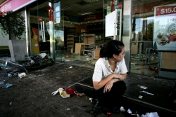 An employee sits amidst a ransacked gas station after looters stole from it